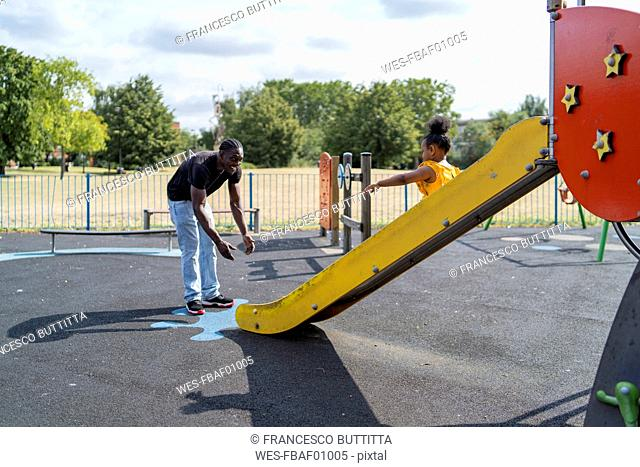 Father with daughter sliding on a playground