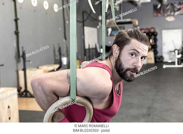 Mixed Race man working out with rings in gymnasium