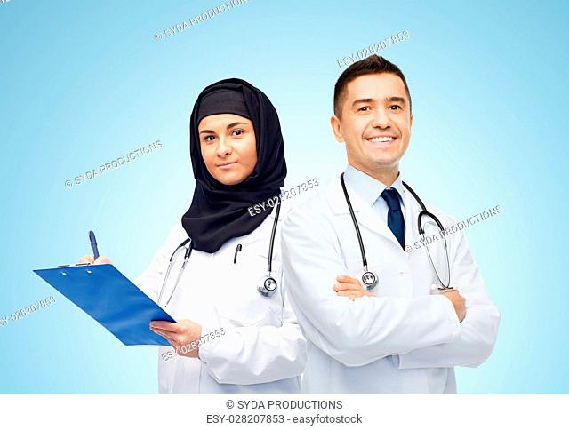 medicine, healthcare and people concept - happy smiling doctors in white coats with clipboard and stethoscopes over blue background