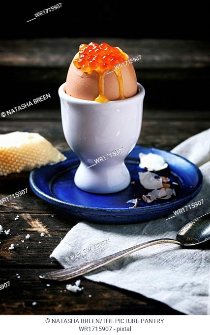 Breakfast with soft-boiled egg with red caviar in white eggcup, served with bread over old wooden table. See series