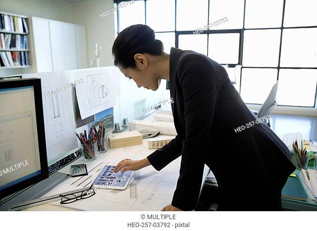 Architect using digital tablet at desk in office