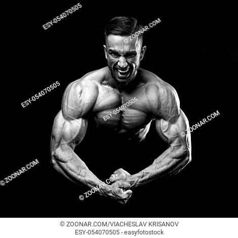 Scream of rage in the bodybuilder during training. Bodybuilding, fitness model. Emotions. On black background. Black and white
