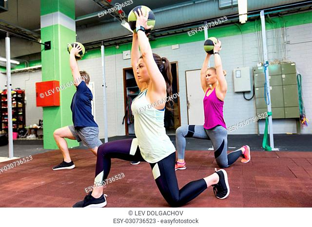 fitness, sport and exercising concept - group of people with medicine balls training in gym