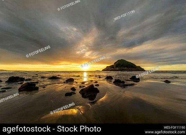 New Zealand, Tongaporutu, Cloudy sky over sandy coastal beach at sunset with Motuotamatea island in background