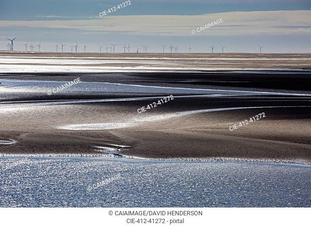 Wind turbines in distance beyond bay, Morecambe Bay, UK