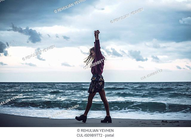 Young woman walking on beach with arms raised at dusk, Odessa Oblast, Ukraine