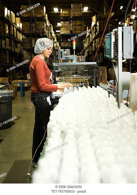 Hispanic female factory worker checking product