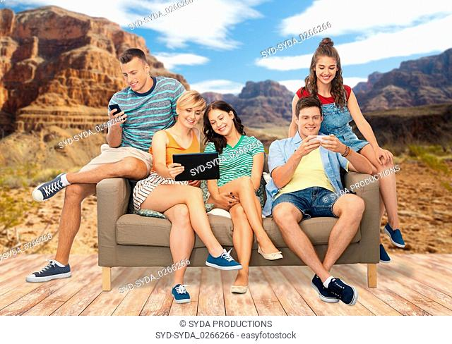 friends with tablet pc and smartphones sit on sofa