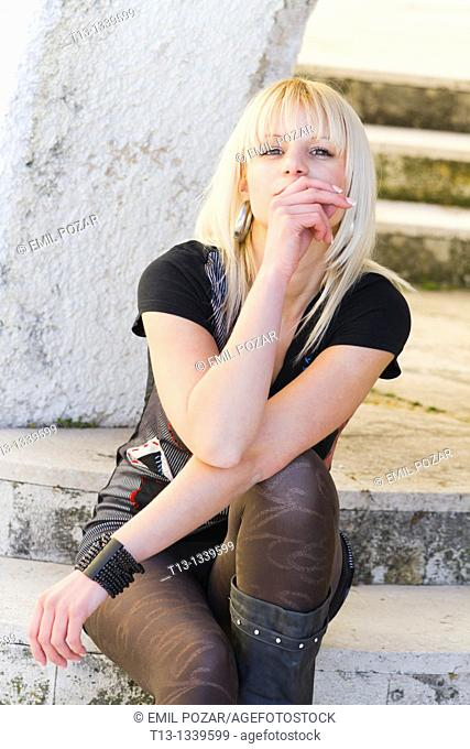 Sitting provocatively on steps young woman
