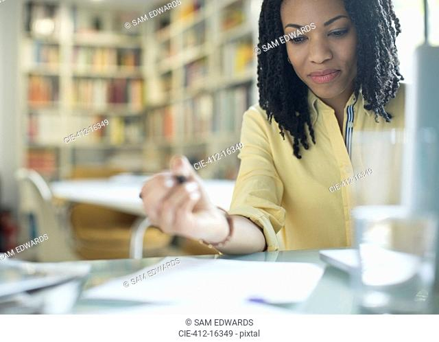 Businesswoman with paperwork at laptop