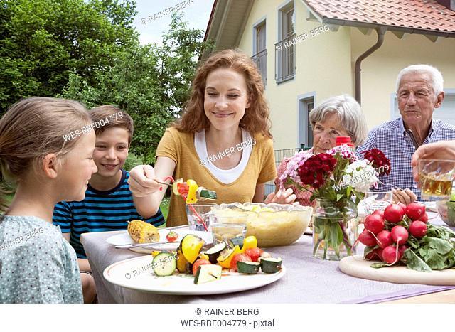 Extended family dining in garden
