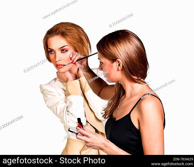 Make-up artist applying lipstick with a brush on model#39;s lips
