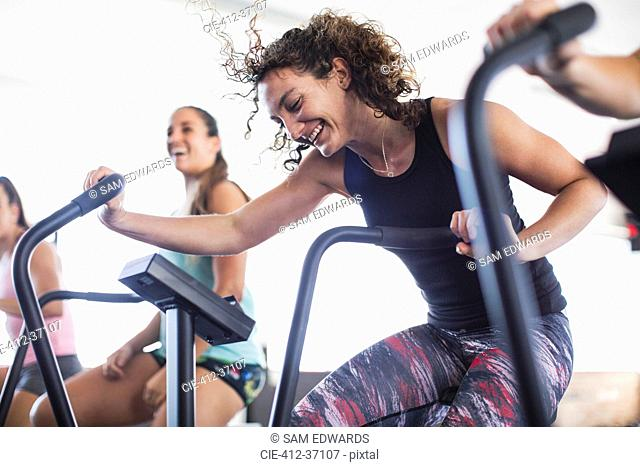 Smiling, playful young woman using elliptical bike in gym