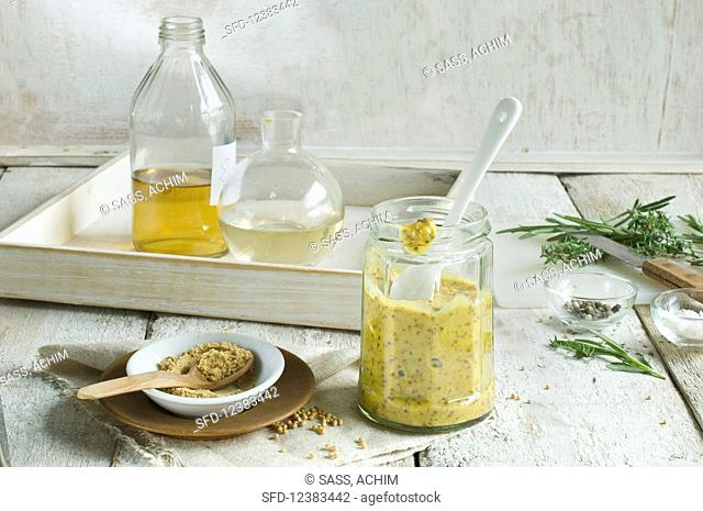 Homemade mustard in a jar with a spoon and the ingredients behind it