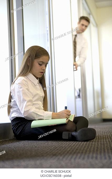 Man checking on young girl coloring in office