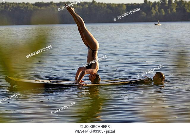 Woman doing a handstand on a paddleboard in a lake