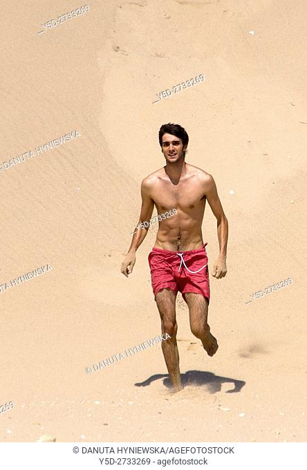 young man on vacation on the beach, here Salema beach, Algarve, Portugal, Europe