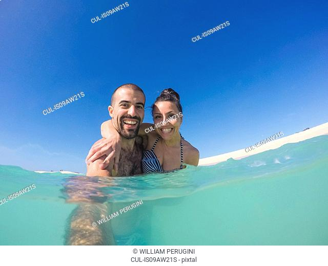 Surface level view of young couple taking selfie in sea