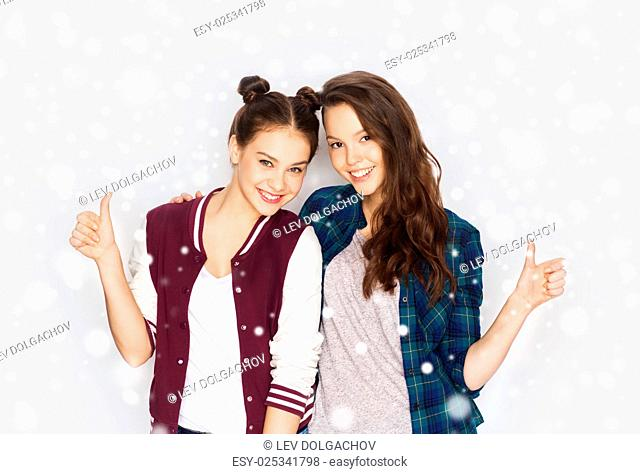 winter, christmas, people, gesture and teens concept - happy smiling pretty teenage girls hugging and showing thumbs up over gray background and snow