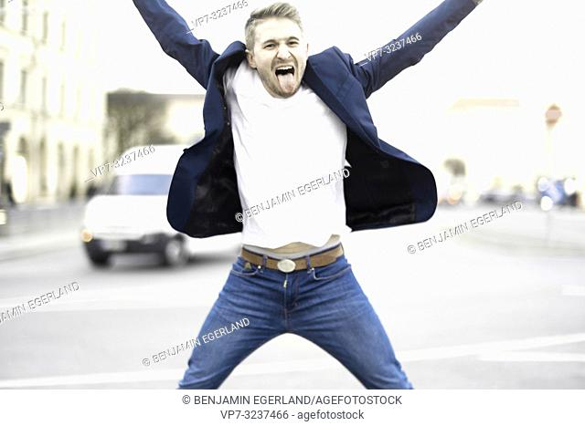 man jumping at street in city, wearing business blazer and jeans, stretching out tongue, in Munich, Germany