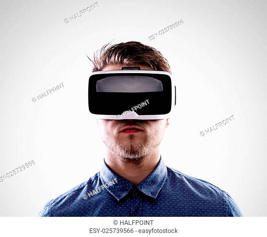 Hipster man in denim shirt wearing virtual reality goggles. Studio shot on gray background