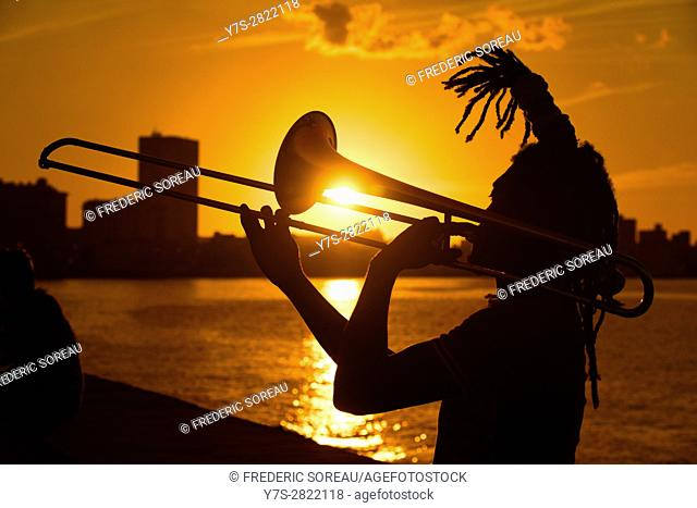 Man playing trumpet in Malecon at sunset, Havana, Cuba