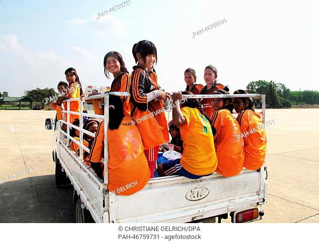 """Members of the women's soccer team """"""""Mighty Girls"""""""" ride to training in the back of a truck in Battambang, Cambodia, 13 February 2014"""