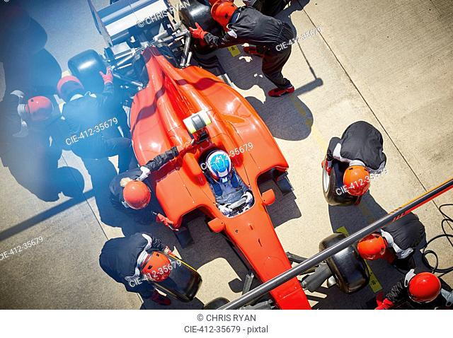 Overhead pit crew working on formula one race car in pit stop