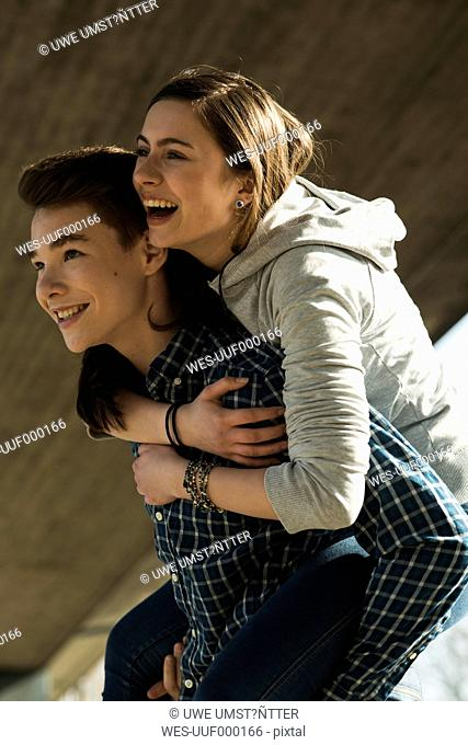 Teenage boy giving his girlfriend a piggyback