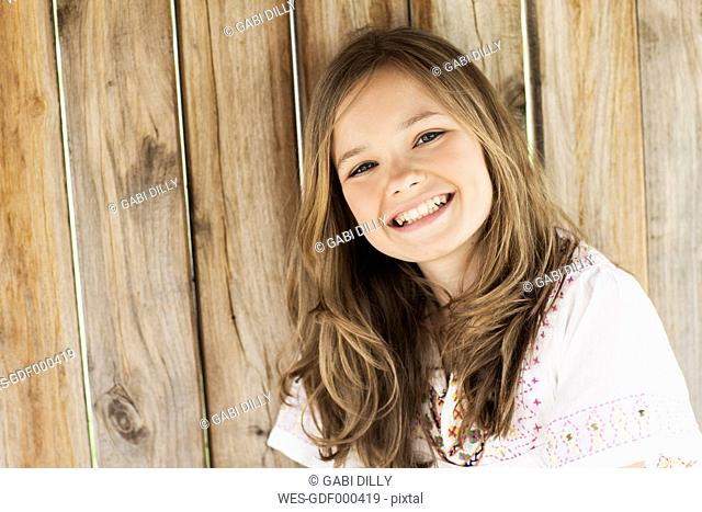 Portrait of smiling girl in front of wooden wall