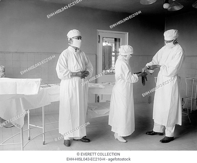 Surgical nurse assists surgeons into rubber gloves before an operation. 1922 in a hospital in Washington, D.C. (BSLOC-2016-10-32)