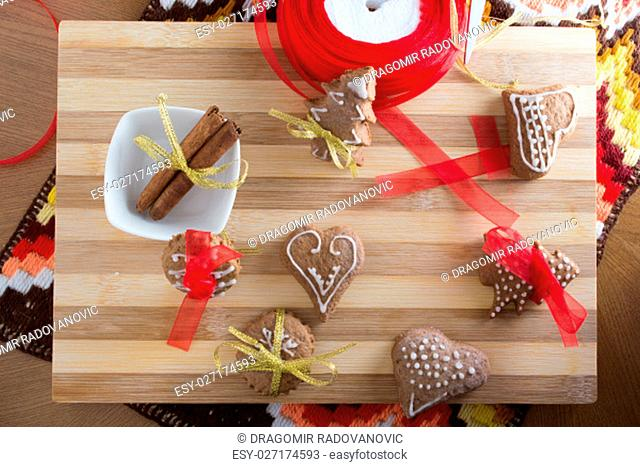 Decorating gingerbread cookies with colourfull ribbons on wooden plate