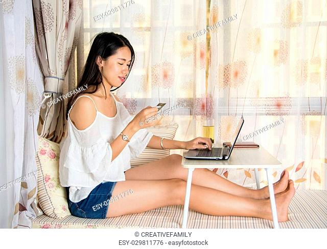 Young woman shopping online sitting by the window