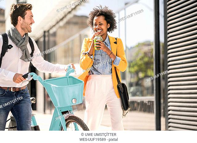 Happy young man and woman with bicycle in the city on the go