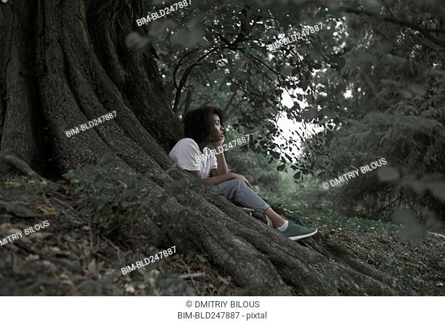 Pensive woman sitting on tree roots in forest