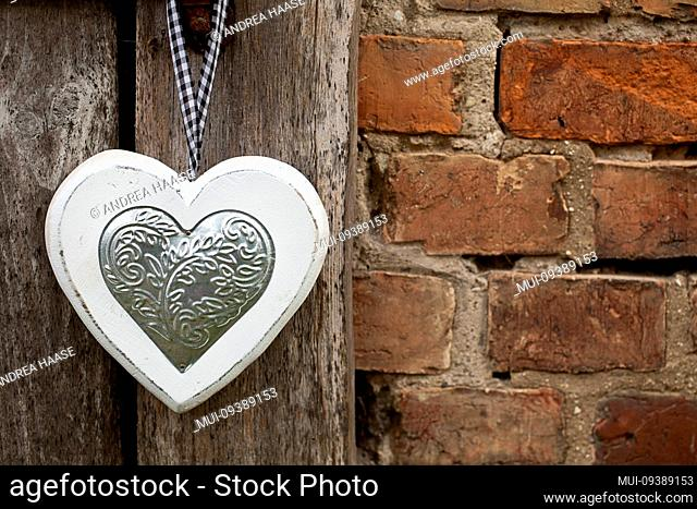 Wooden heart with silver application hanging on old barn door with copy space