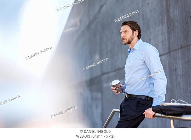 Businessman with laptop bag and takeaway coffee leaning against a railing