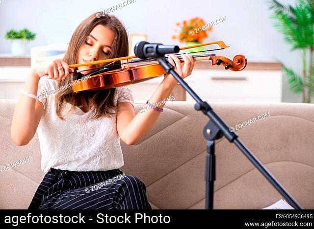 Female beautiful musician playing violin at home