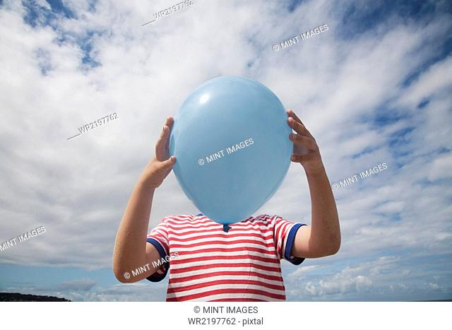 A boy standing holding a balloon in front of his face