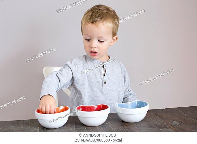 Little boy reaching into bowl