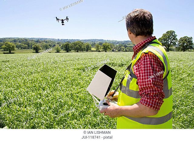 Farmer flying drone to survey crop in field