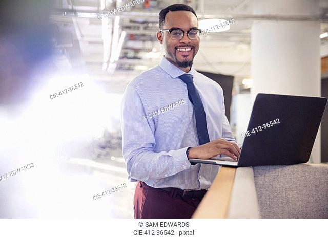 Portrait smiling businessman using laptop in office