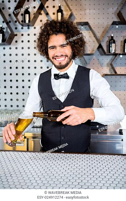 Bartender pouring beer in glass