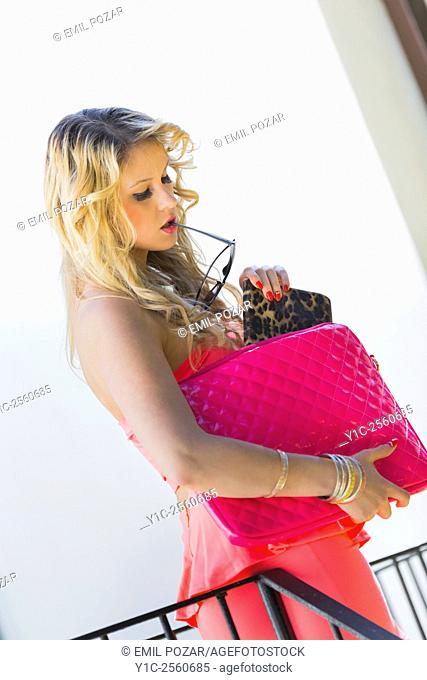 Fanciful lady spontaneous pulling wallet from handbag