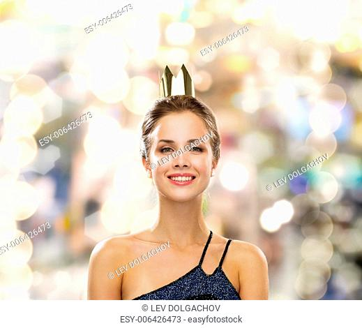 people, holidays, royalty and glamour concept - smiling woman in evening dress wearing golden crown over lights background