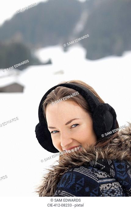 Close up portrait of woman wearing earmuffs in snowy field