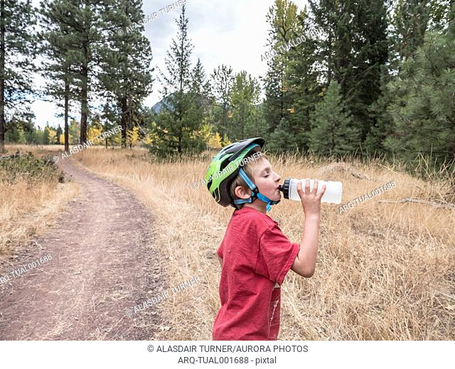 A young boy on a bike ride stops to drink some water
