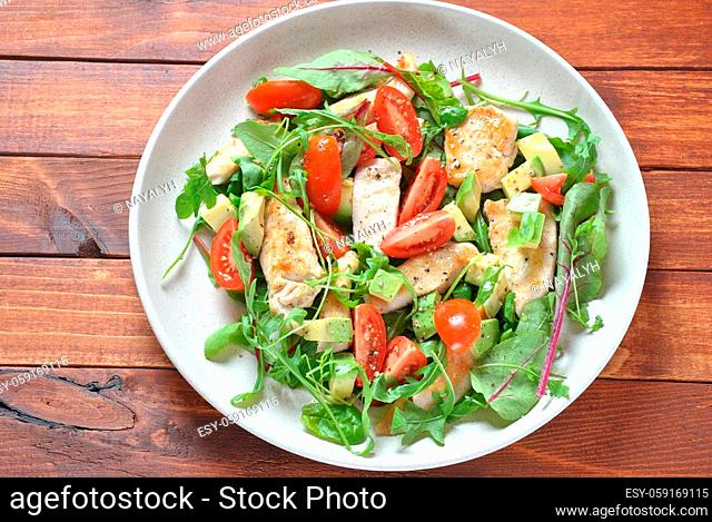 Chicken salad with avocado and cherry tomatoes, arugula and beet leaves