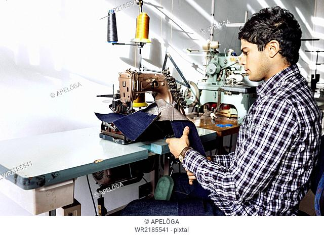 Tailor sewing jeans in factory