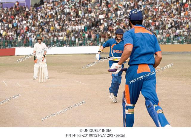 Two cricket batsmen running between the wicket for run